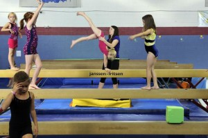 CASTLE ROCK, CO - SEPTEMBER 17: Jessie Kaehn, center, helps a student on the balance beam at the Castle Rock School of Gymnastics on September 17, 2014, in Castle Rock, Colorado. Lexy Gabriel took over ownership of the school in August 2006. (Photo by Anya Semenoff/The Denver Post)